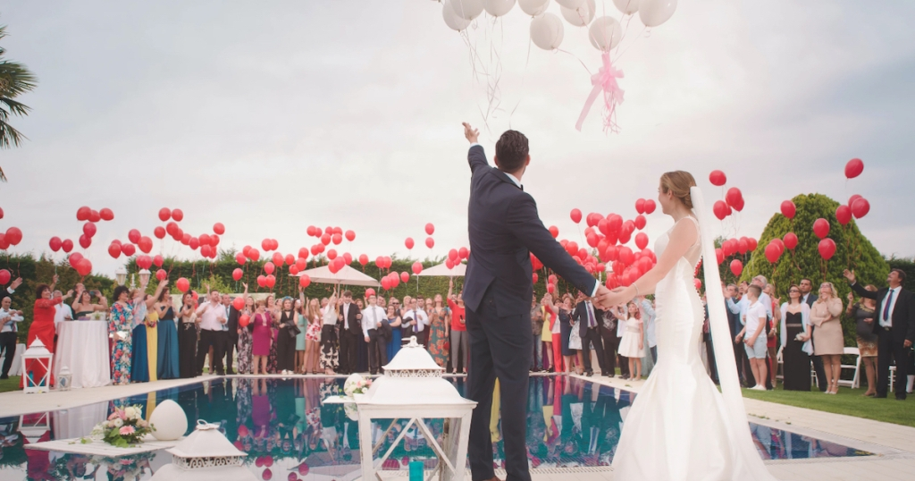 bride and groom standing around pool with their wedding party and tons of balloons