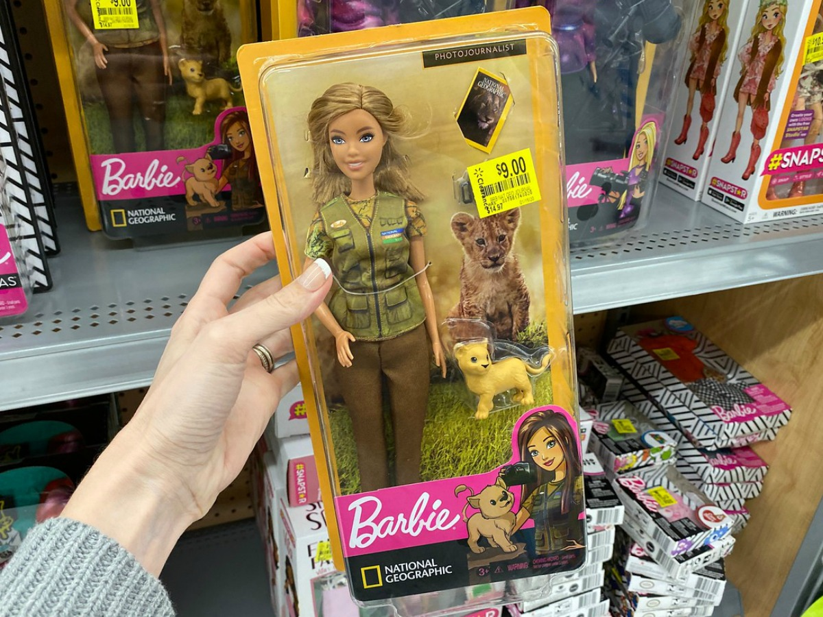 hand holding barbie doll in package at store