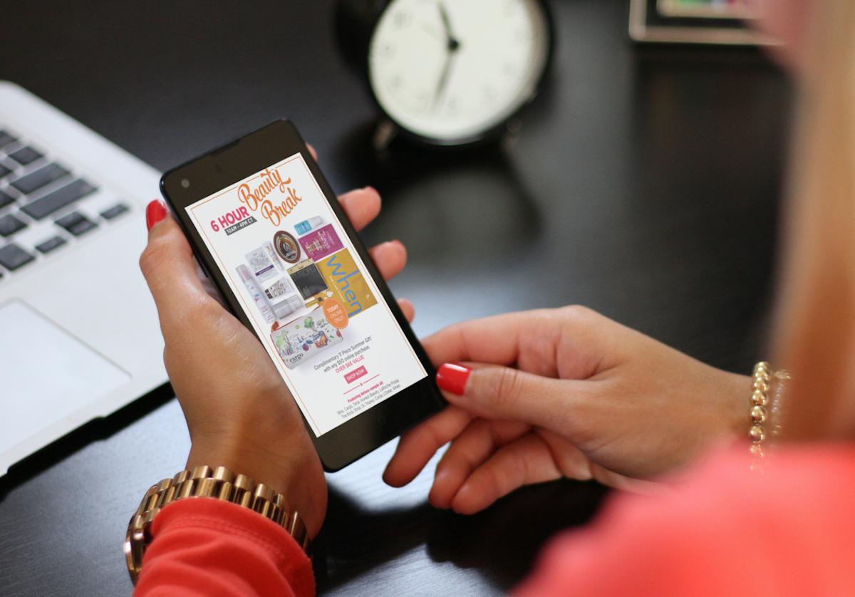 woman holding phone with ulta sale beauty break info on screen