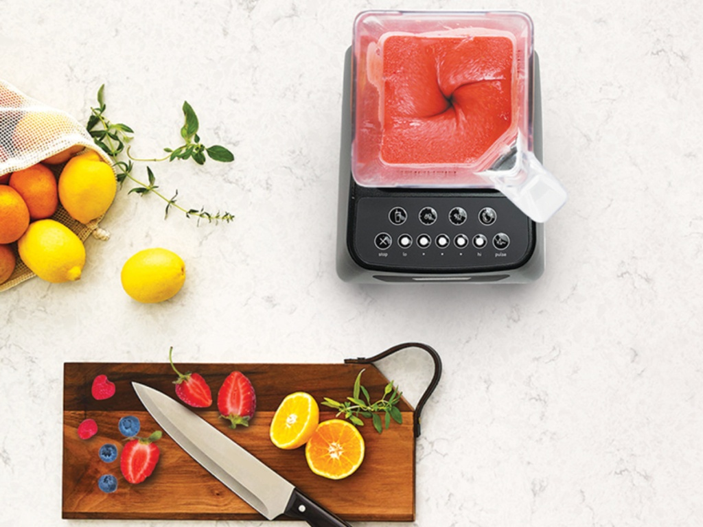 overhead view of blendtec with smoothie in blender and cutting board with fruit