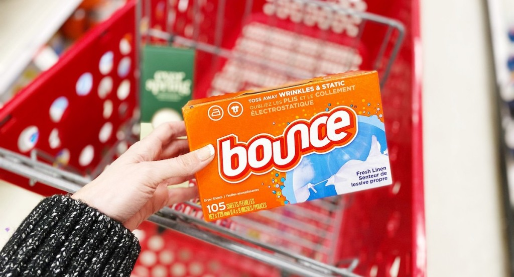 hand holding orange box of bounce dryer sheets with target cart in background