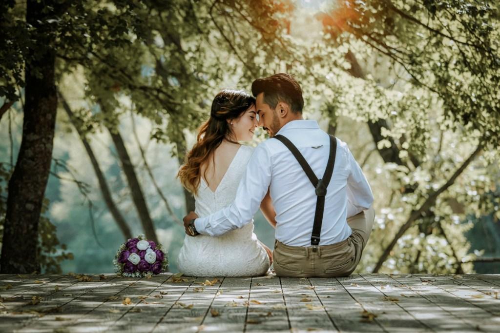 wedding couple sitting on bridge