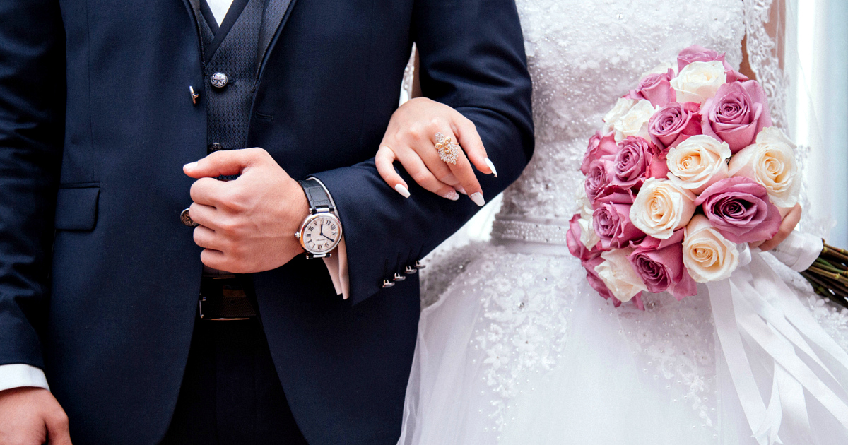 man and woman holding arms together at wedding