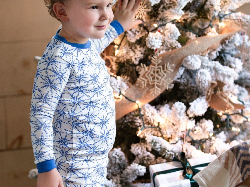 toddler boy in icicle pajamas standing by Christmas tree