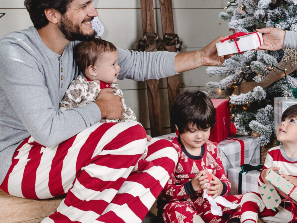 man wearing red and white striped pajama pants and grey thremal holding baby and passing out a gift