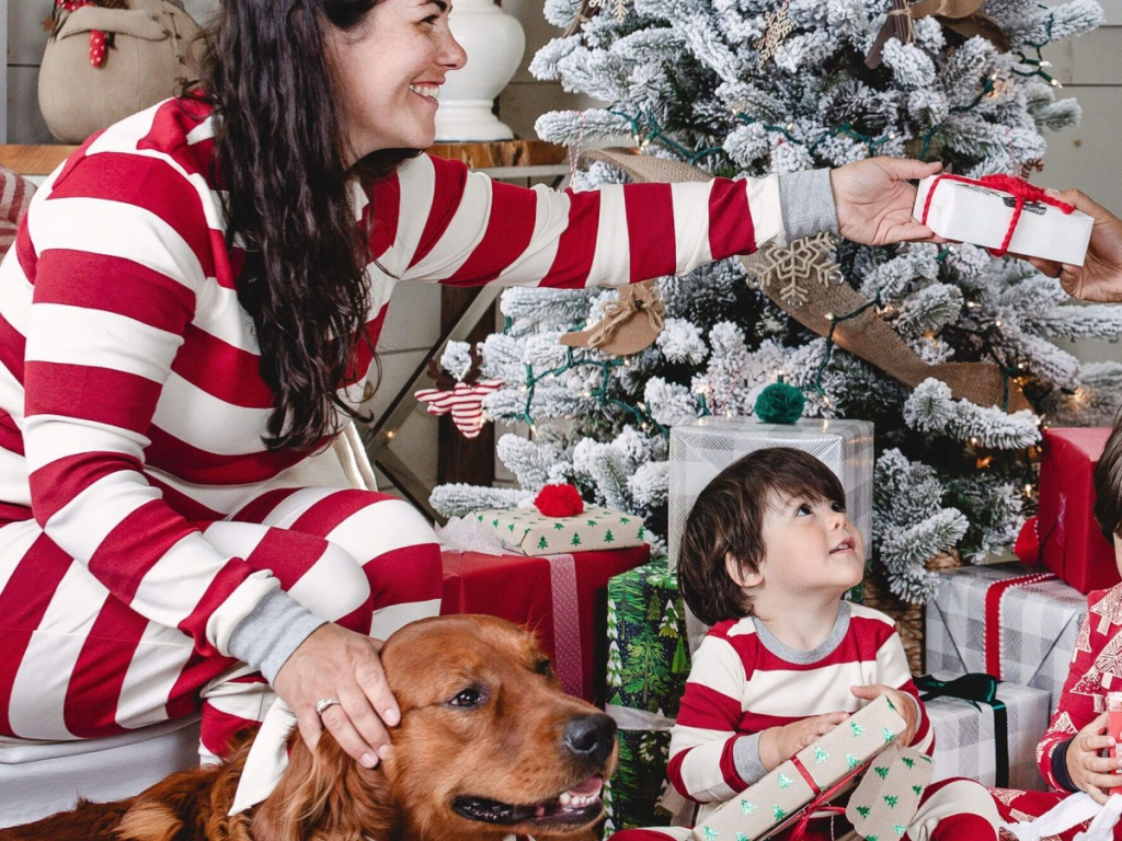 woman wearing red and white striped pajamas handing out gifts by the tree
