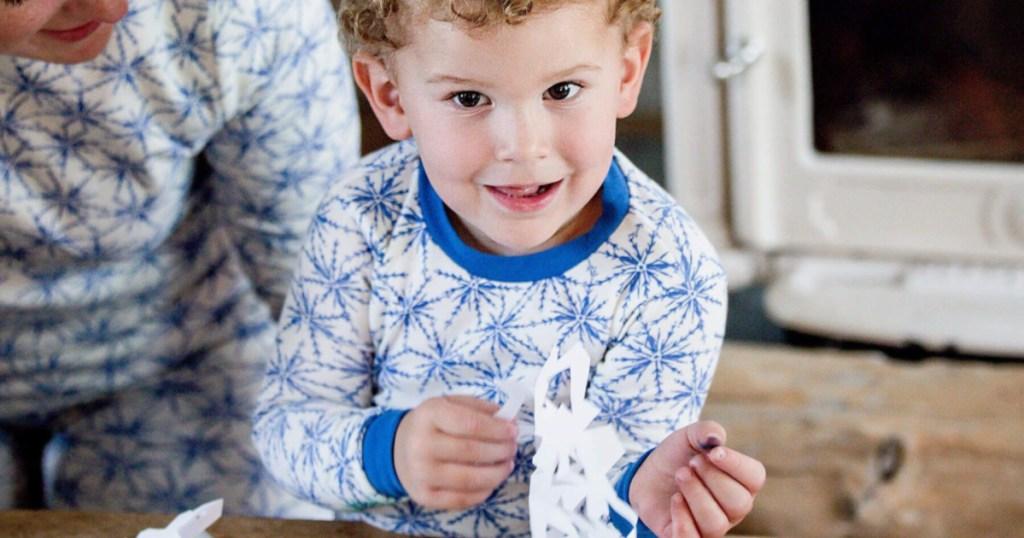 toddler boy wearing blue and white snowflake pjs making paper snowflakes