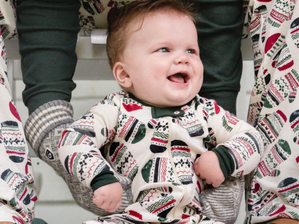 man holding up baby wearing mittens pajamas