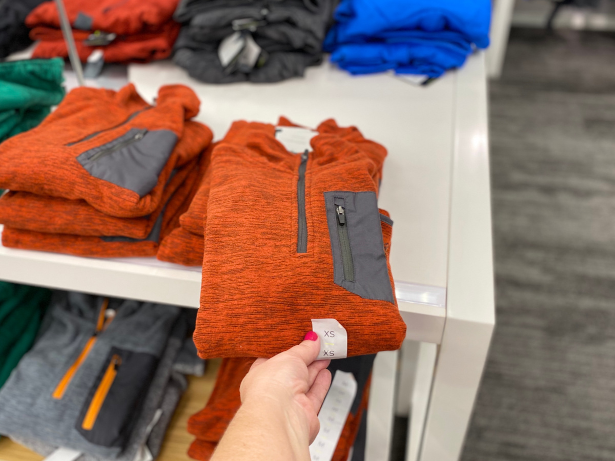 hand holding orange active shirt with clothing in background