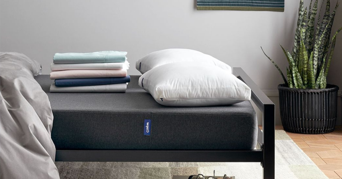 stack of sheets and pillows on bed in bedroom