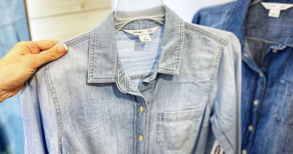 hand holding a light colored chambray denim shirt