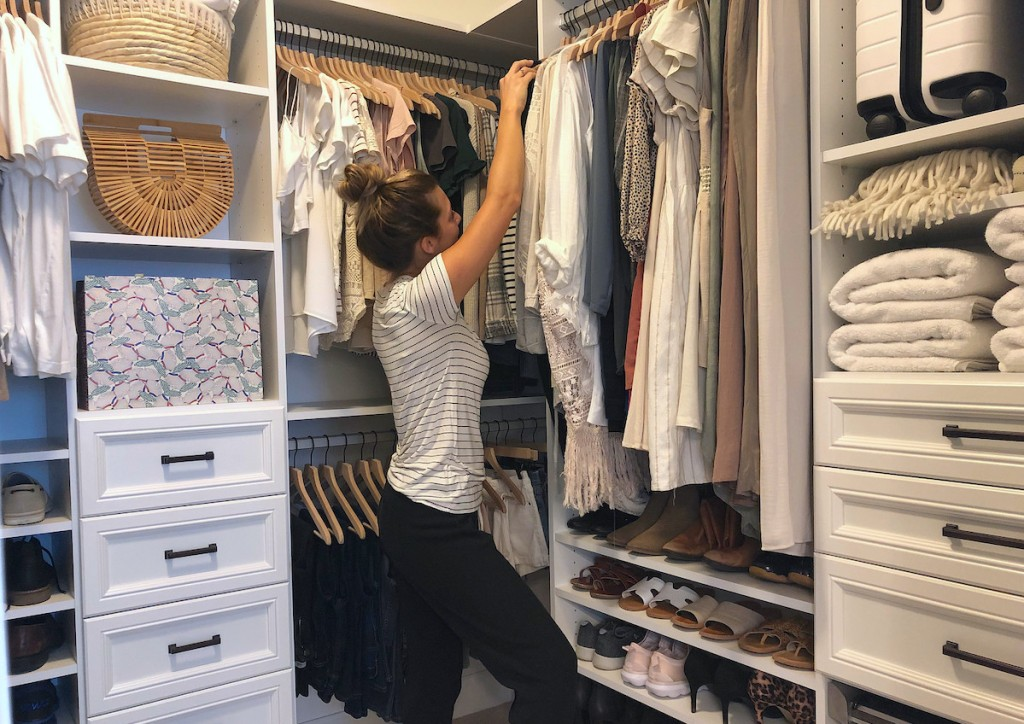 woman standing in walk-in closet with clothes and organized shoes