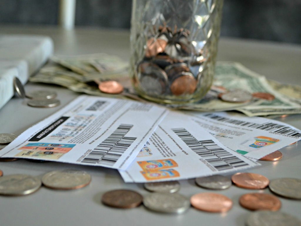coupons sitting on table with jar of change