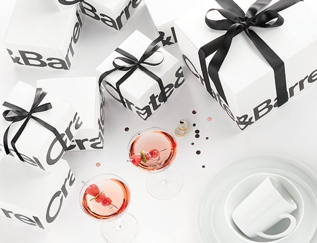 white and black crate and barrel wedding registry gifts with black ribbon and two cocktail drinks