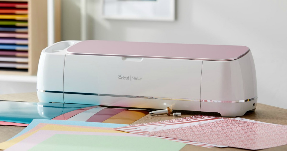 die cute machine with pink top on table by colored papers