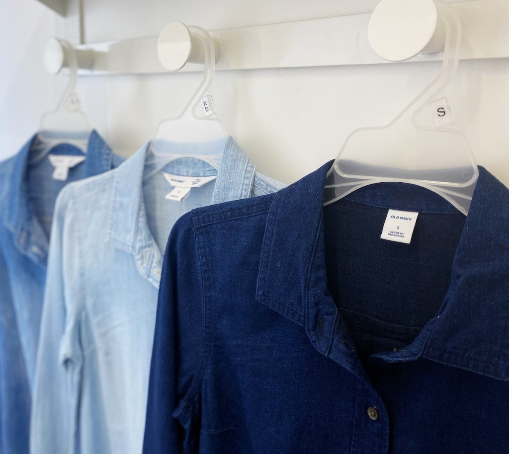 row of dark medium and light chambray shirts on white handers