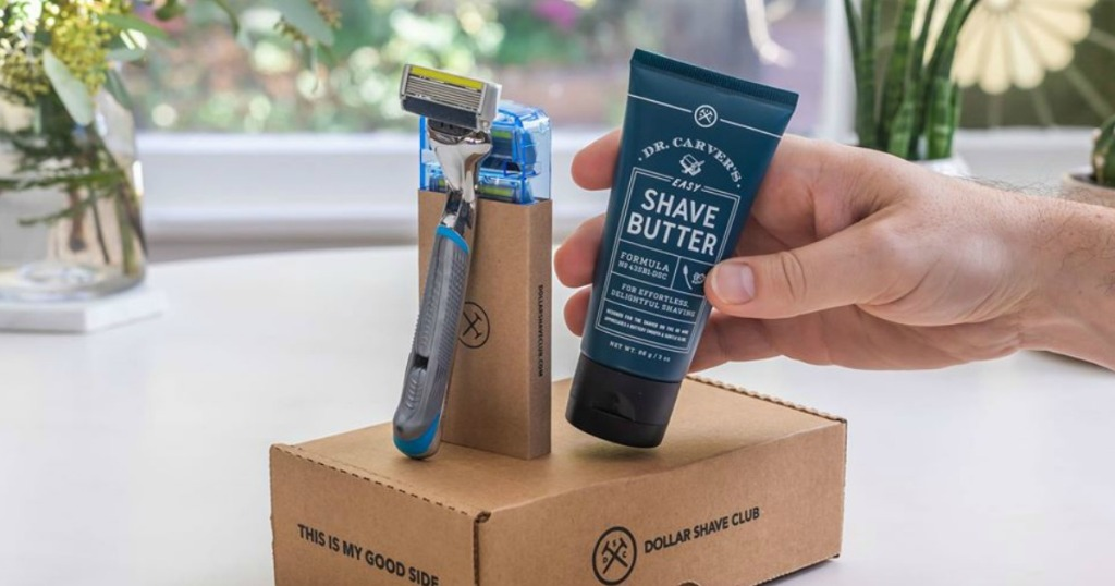 hand holding shave butter next to box with razor on bathroom sink