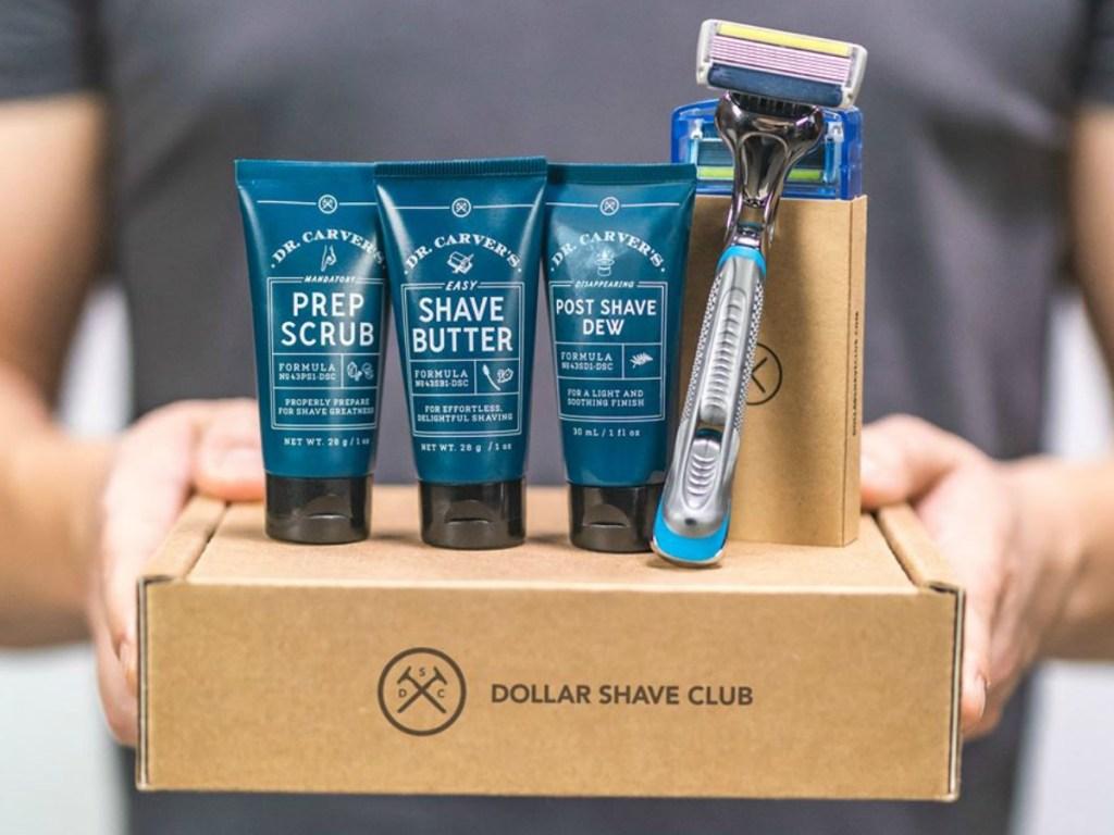man holding box with razor and shaving cream on it