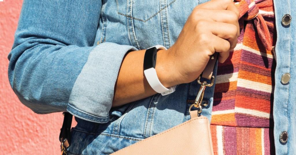 woman in jean jacket wearing white fitbit on arm