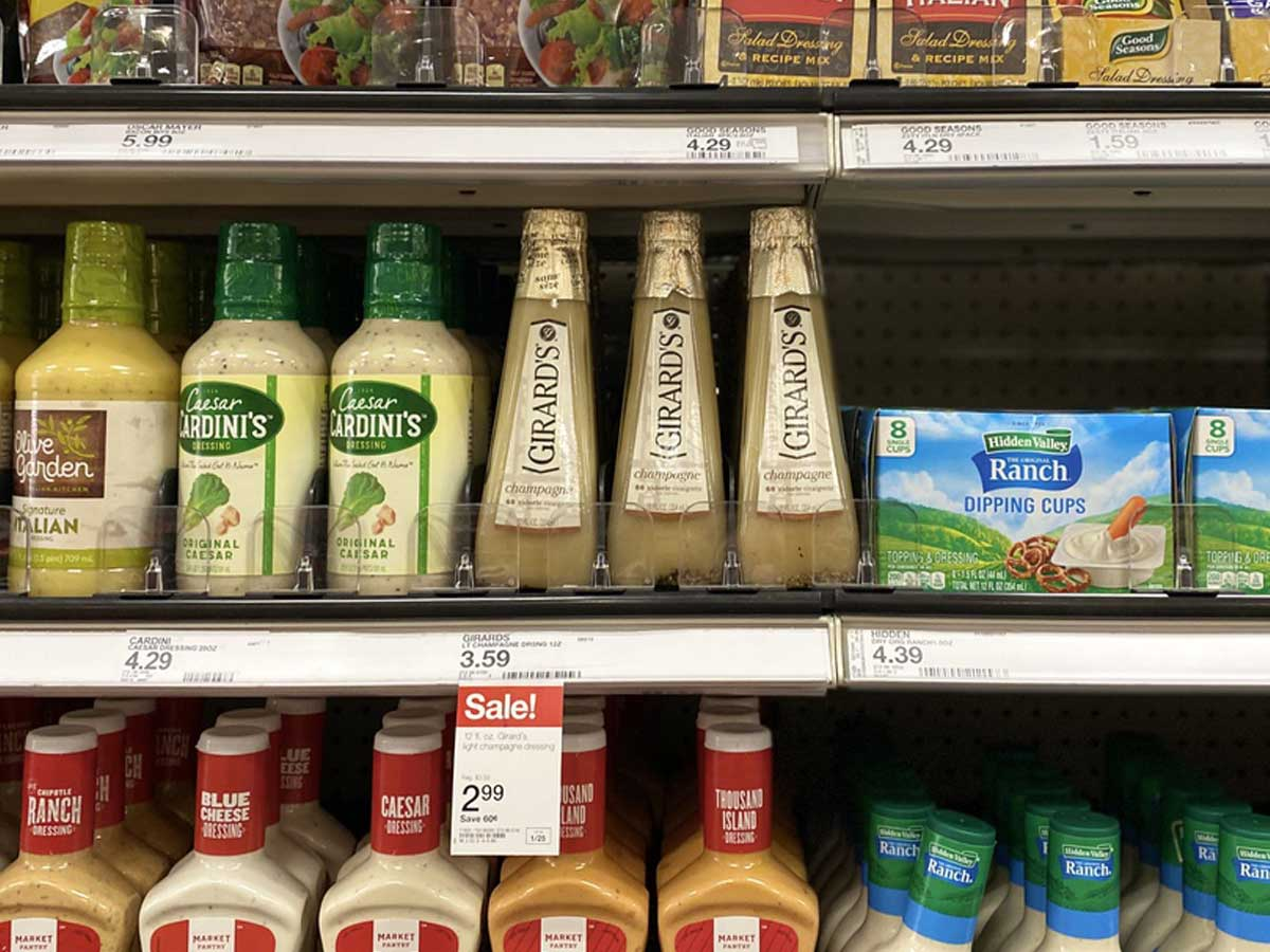 bottles of salad dressing on a shelf in a store with sale tags
