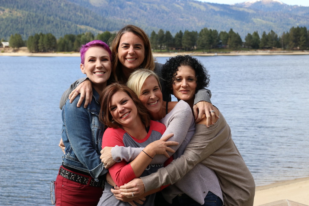 5 woman hugging and smiling with lake in background