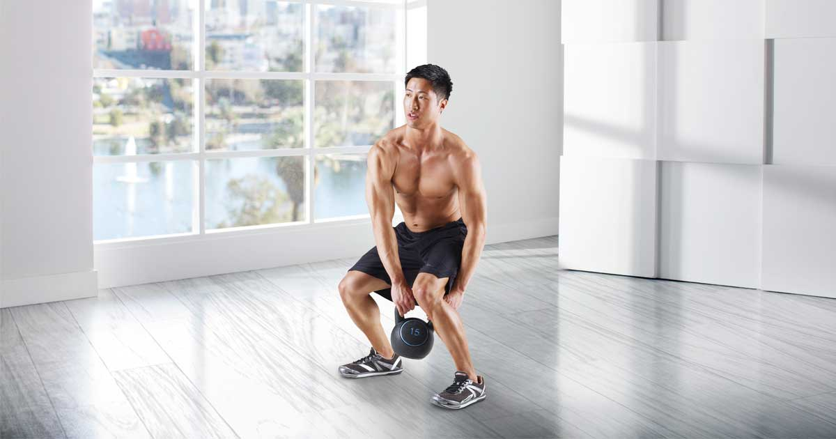 man in room using a Gold's Gym Kettlebell