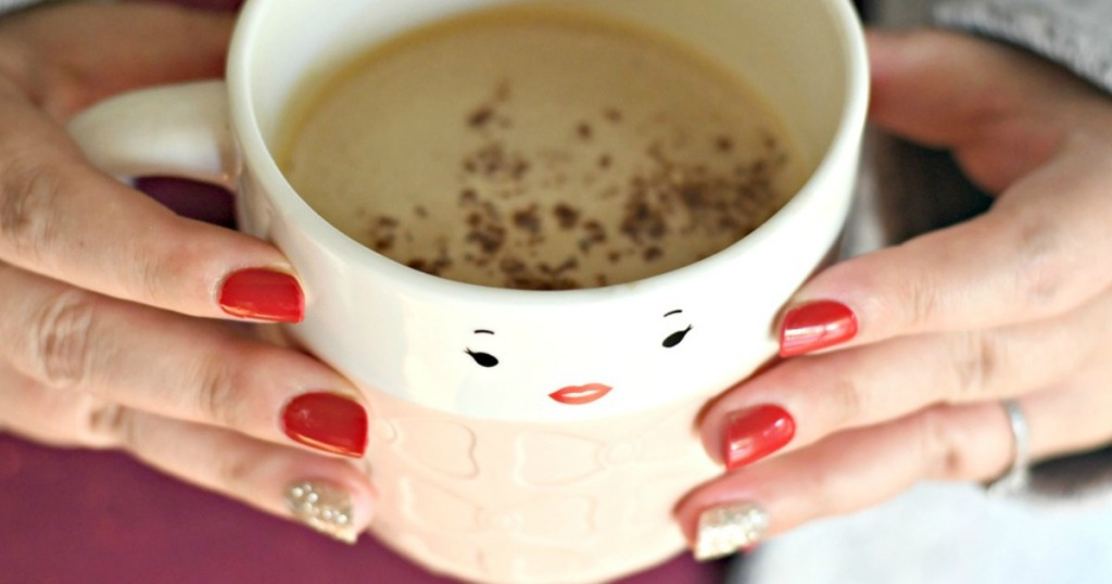 women holding coffee cup with painted nails