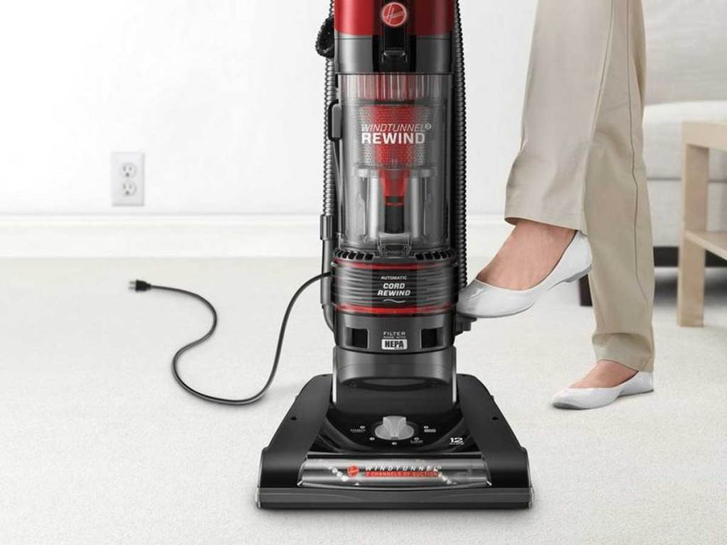 woman standing next to Hoover WindTunnel 2 Rewind Pet Upright Bagless Vacuum