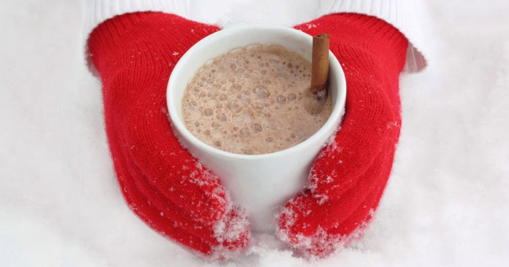 Hands wearing red mittens holding a cup of hot cocoa in the snow