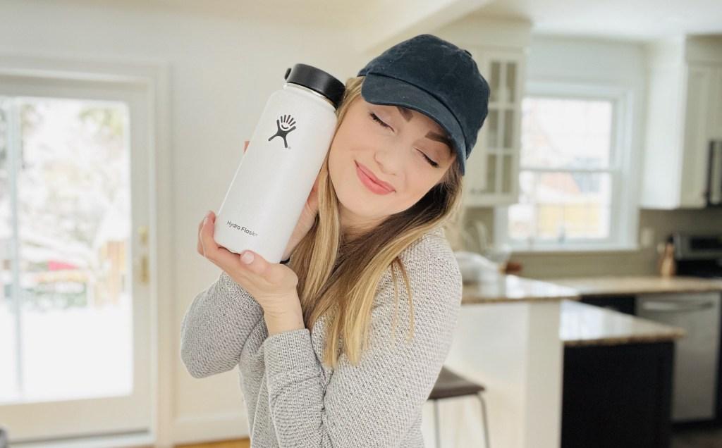 woman holding white hydro flask bottle