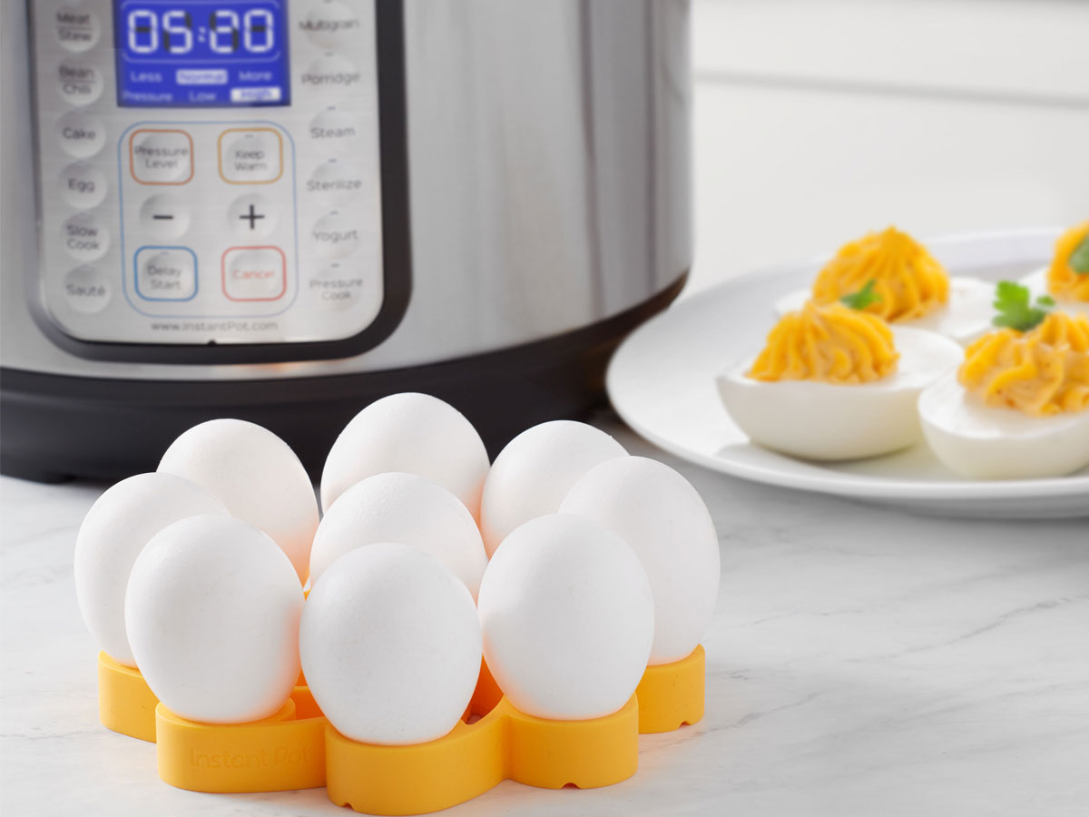 Instant Pot Official Silicone Egg Rack with a dozen eggs on it, an instant pot in background and deviled eggs