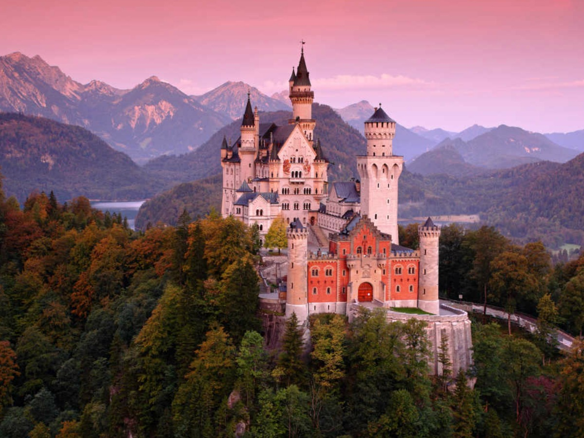 castle near the mountains and trees with pink sunset