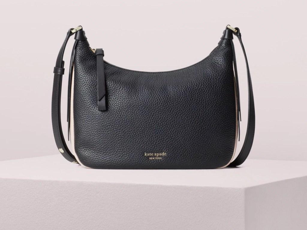black kate spade handbag with pink background