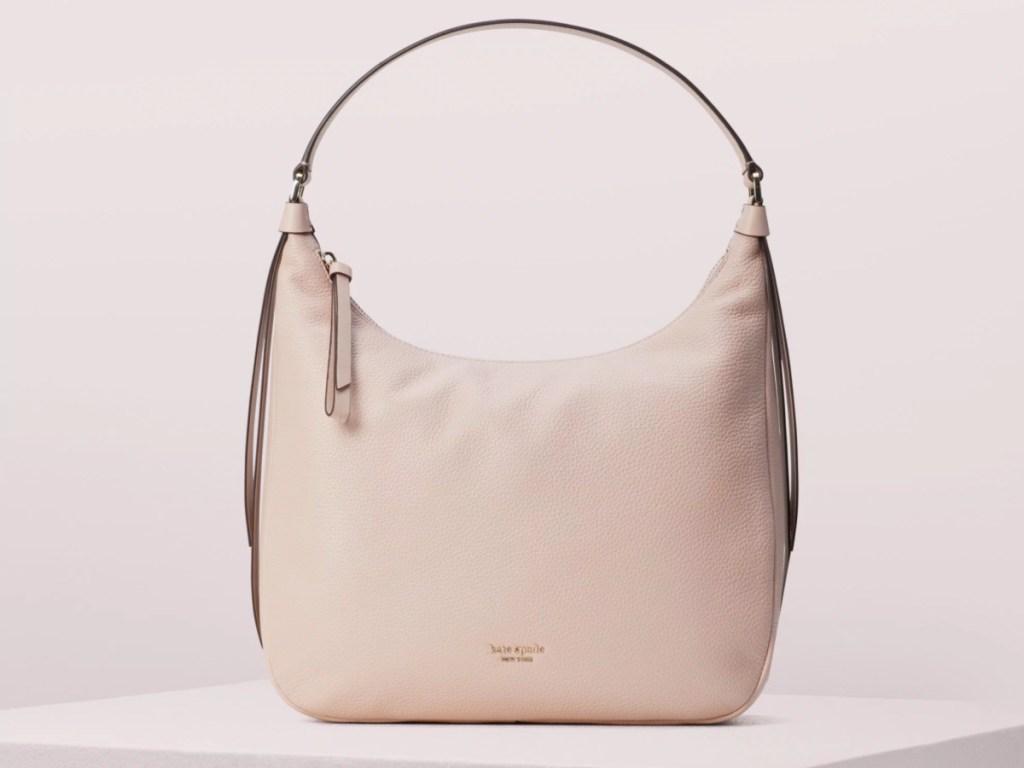 peach kate spade handbag with pink background