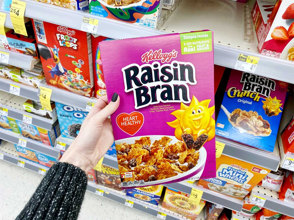 hand holding a brand name box of cereal in a store