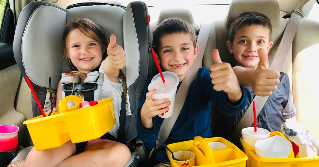 kids in car with yellow school caddies on laps with chick fila food inside