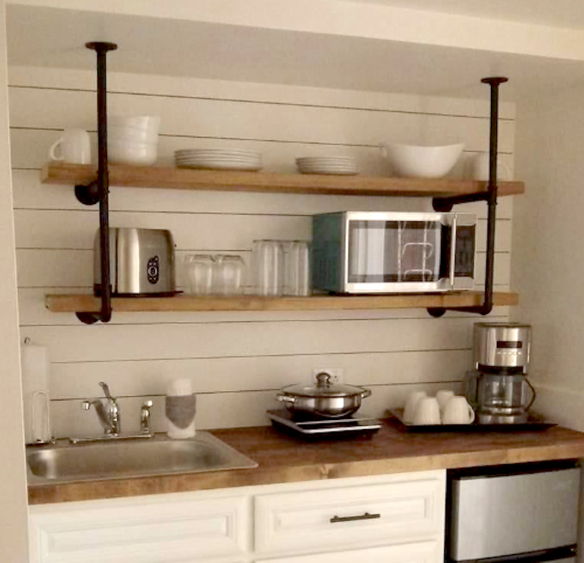 kitchen wall with shiplap and wood and iron pipe shelves with dishes on them