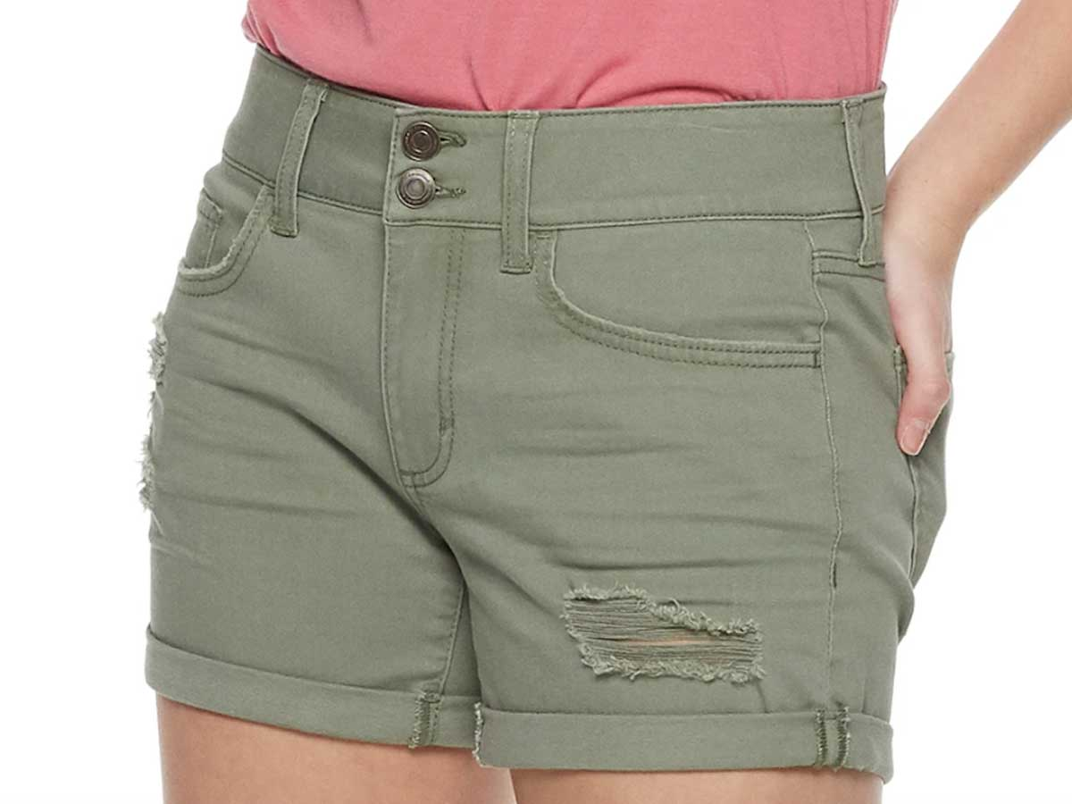 model wearing a pair of olive green juniors' so 2 button denim midi shorts from Kohls