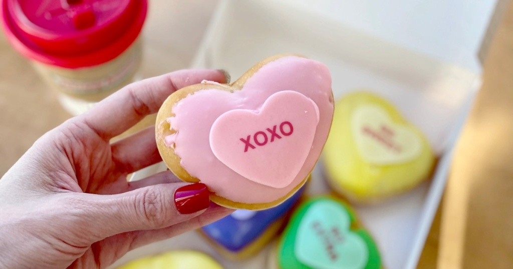hand holding heart-shaped doughnut with pink frosting