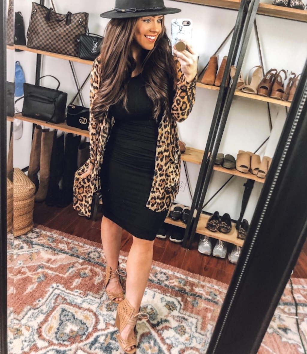 woman wearing black dress and leopard cardigan and black hat