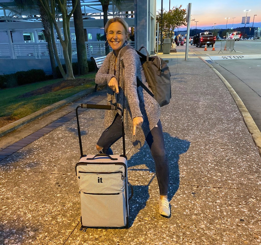 woman holding carry on luggage and bookbag on sidewalk
