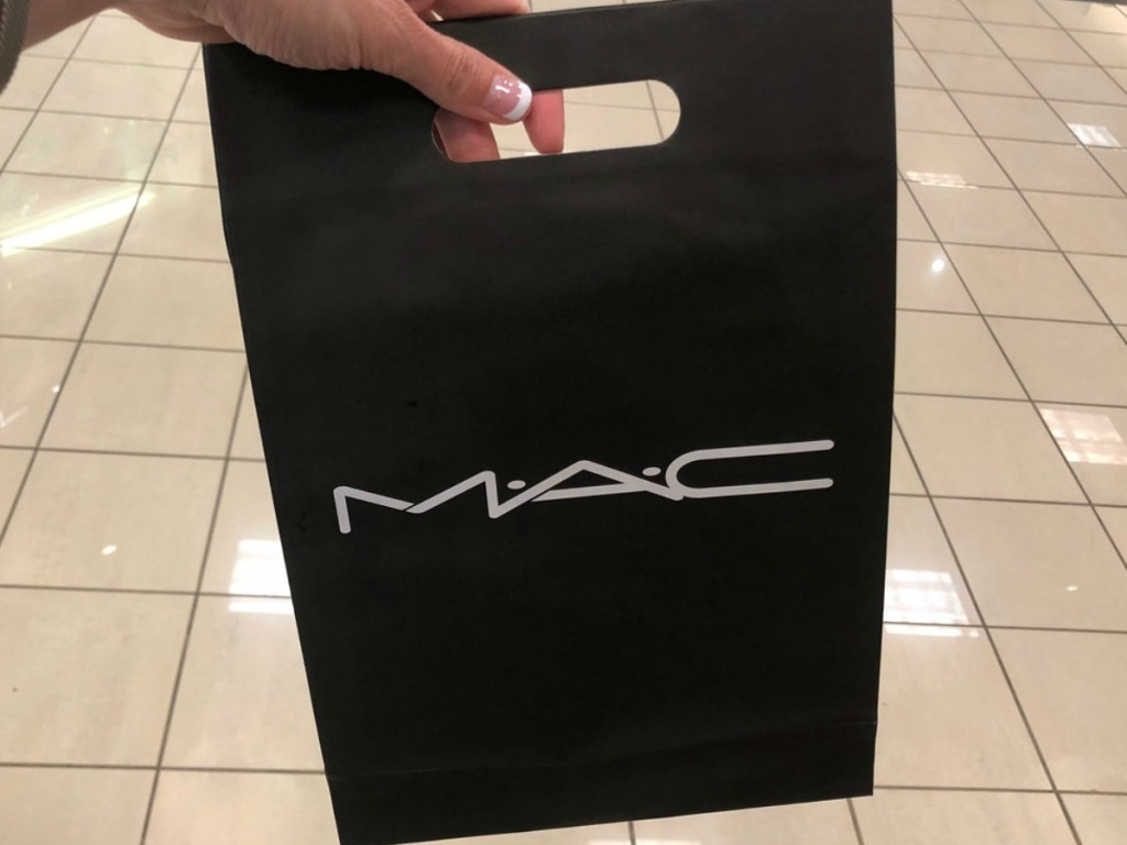 hand holding black bag in store that says MAC