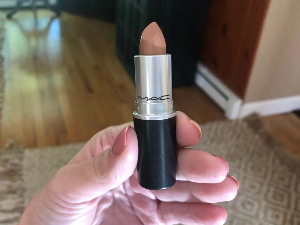 hand holding tube of lipstick in home