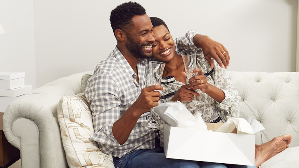 man and woman happy and smiling sitting on couch with champagne glasses