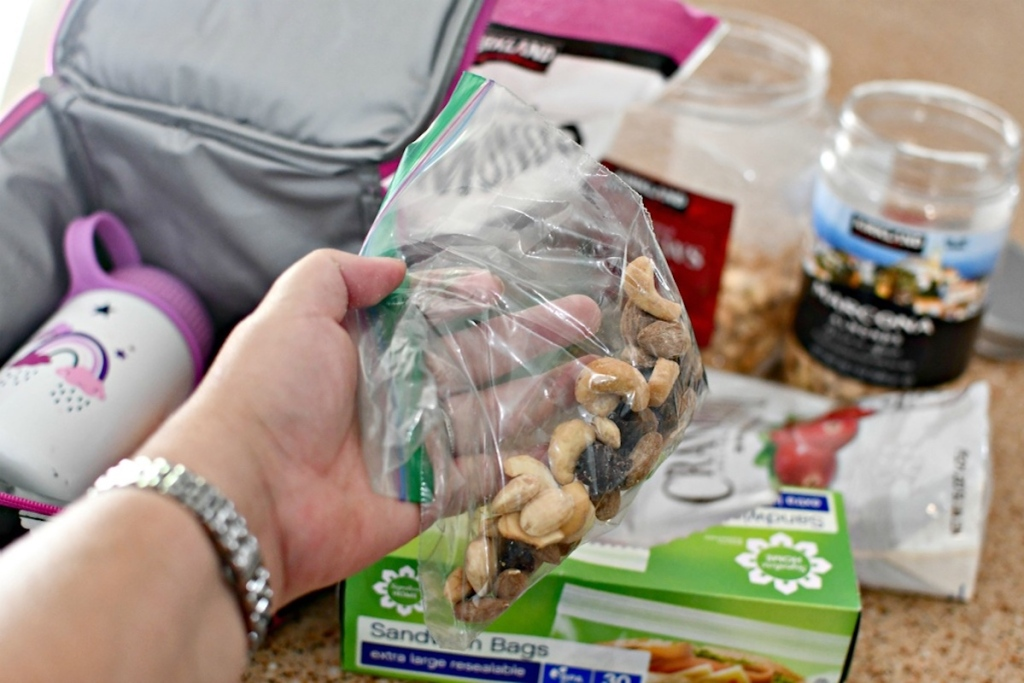 hand holding waste of money plastic baggie with trail mix