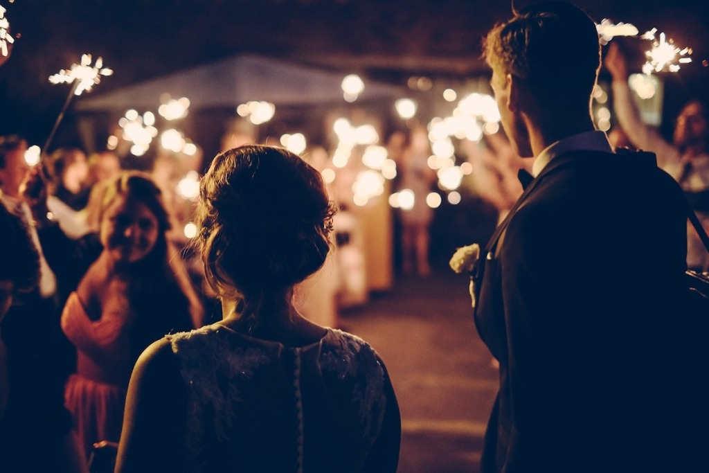 couple bride and groom standing with guests in dark with sparklers