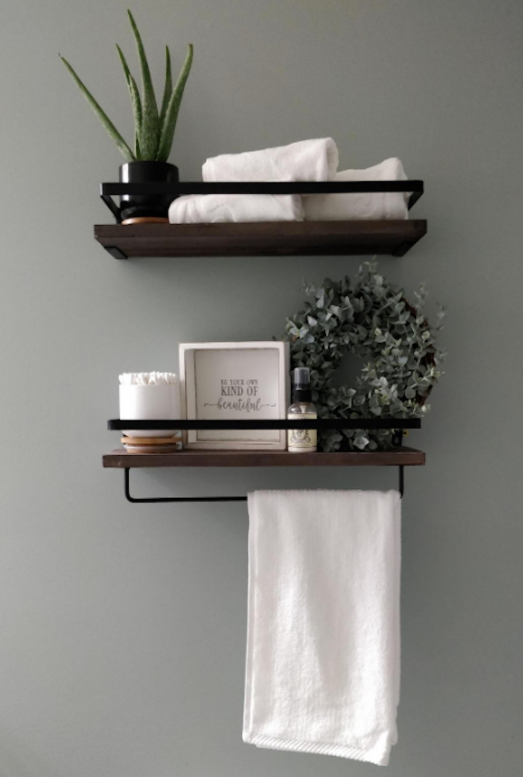 two wood and black shelves with bathroom decor hanging on wall