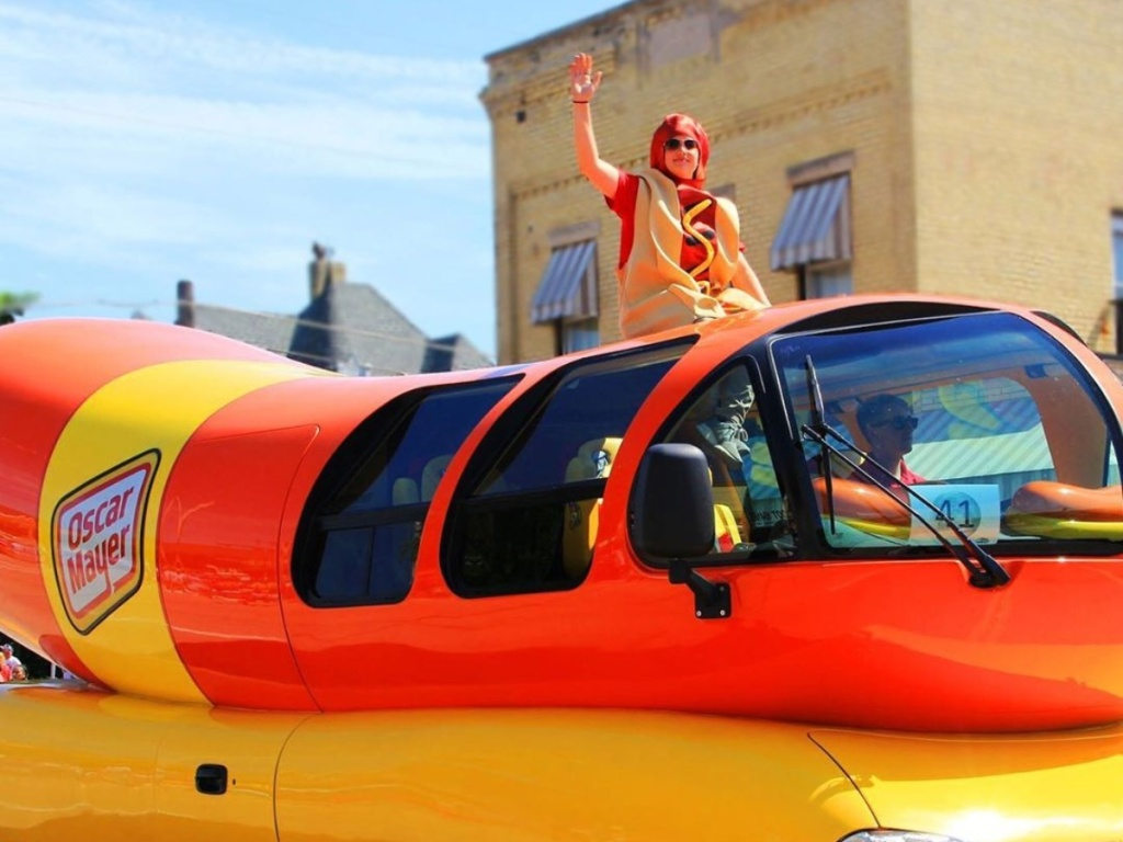man in hot dog costume riding on Weinermobile