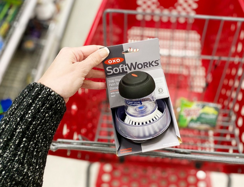 hand holding a oxo brush in package with target cart in background
