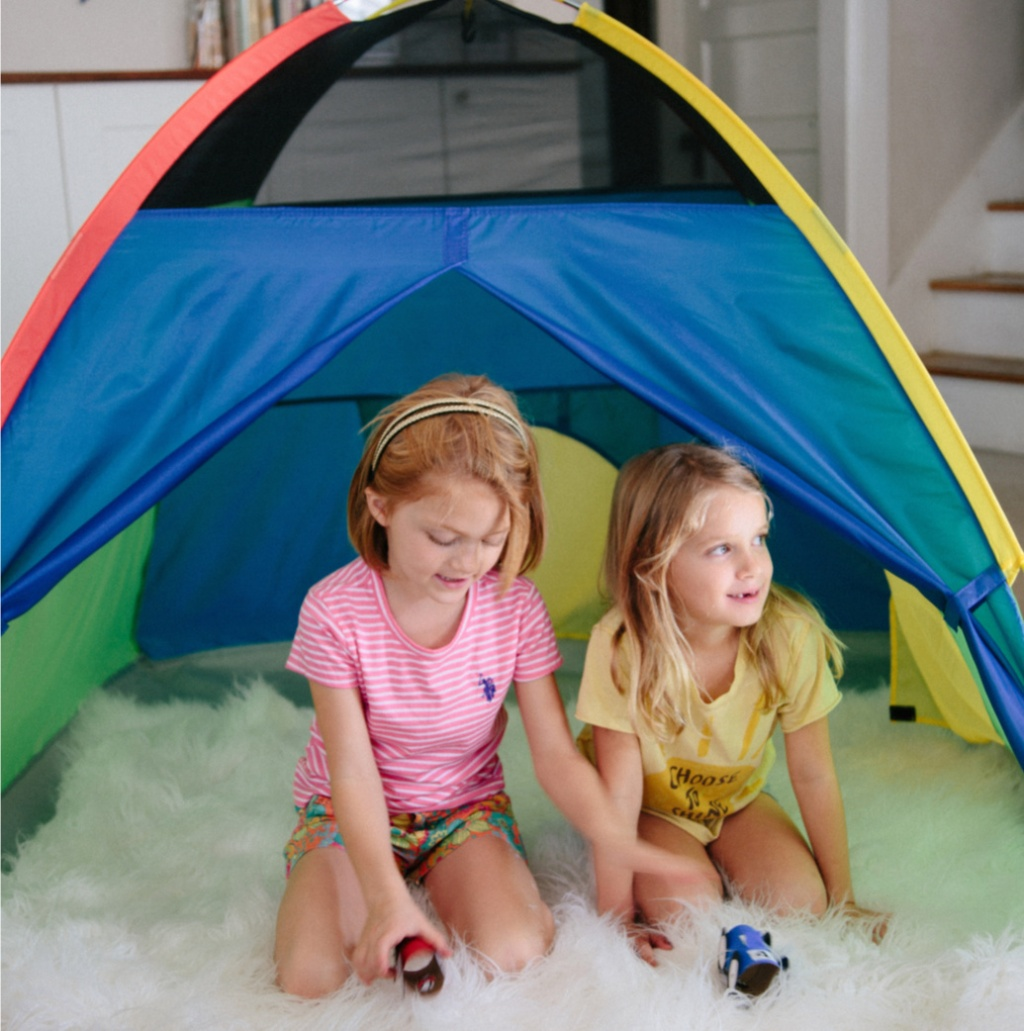 girls playing in play tent on white fluffy blanket